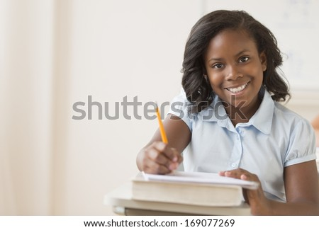 Portrait of girl smiling while writing notes in book at classroom desk - stock photo