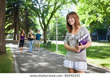 Portrait of girl standing with a book while her friends walking in background - stock photo