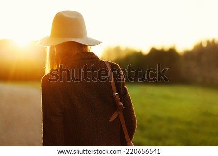 Portrait of girl walking down the countryside road in sunset light. Back to camera. Outside - stock photo