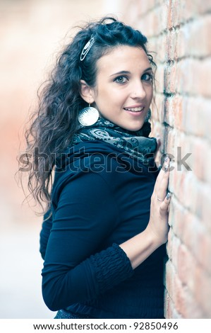 Portrait of girl wearing blue sweater leaning against the wall. Shallow DOF.