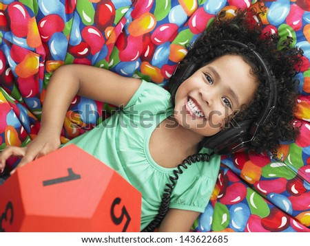 Portrait of girl wearing headphones and holding twelve-sided dice while reclining on beanbag - stock photo