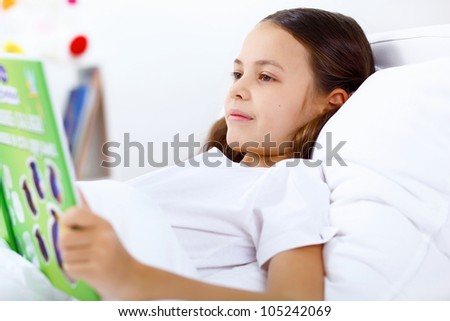 Portrait of girl with a book in bed at home