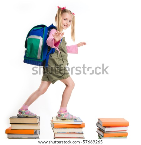 Portrait of girl with backpack walking from top to top of book piles - stock photo