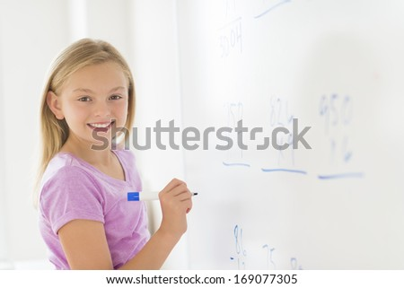 Portrait of girl with felt tip pen smiling while standing by whiteboard in classroom - stock photo