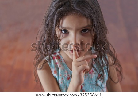 Portrait of girl with finger on lips