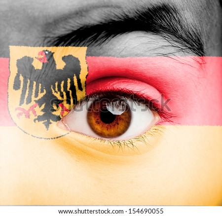 portrait of girl with german flag painted on her face