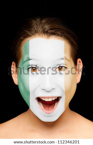 portrait of girl with irish flag painted on her face - stock photo