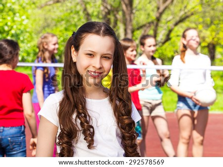 Portrait of girl with teens playing volleyball