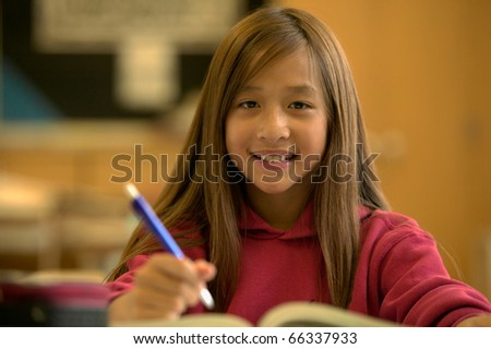 Portrait of girl writing at desk - stock photo