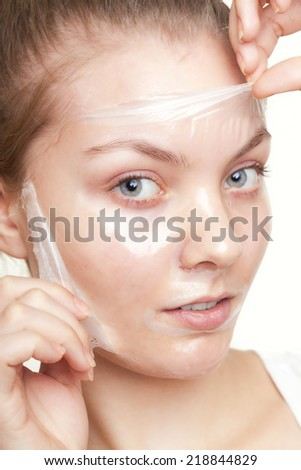 Portrait of girl young woman in facial peel off mask isolated on white. Peeling. Beauty and body skin care. Studio shot. - stock photo