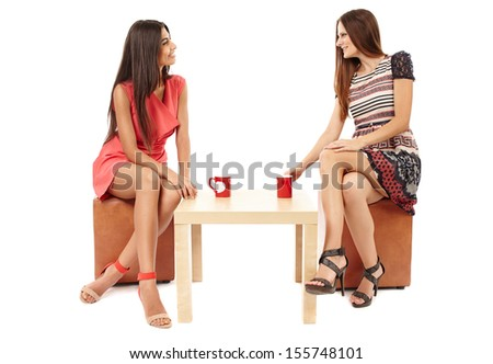 Portrait of girlfriends gossiping and talking over a cup of tea isolated on white - stock photo