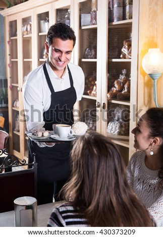 Portrait of girls chatting in coffee-house and cheerful smiling waiter