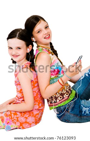 Portrait of girls listening to MP3 player and smiling isolated over white - stock photo