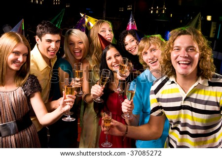 Portrait of glad people in smart clothing toasting at birthday party - stock photo