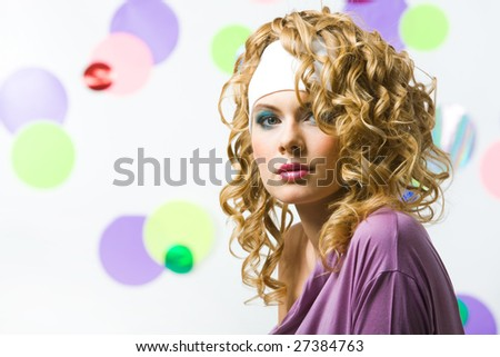 Portrait of glamorous blonde with wavy hair-style looking at camera on colorful background - stock photo