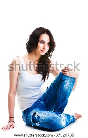 Portrait of glamorous young pretty woman wearing blue jeans sitting on white floor - stock photo
