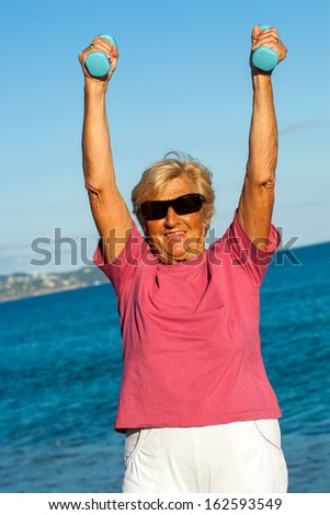 Portrait of golden age female shaping up on beach. - stock photo