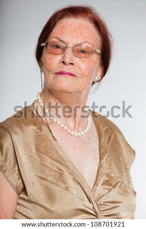 Portrait of good looking senior woman wearing glasses with expressive face showing emotions. Smiling. Acting young. Studio shot isolated on grey background.