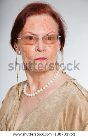 Portrait of good looking senior woman wearing glasses with expressive face showing emotions. Acting young. Studio shot isolated on grey background.