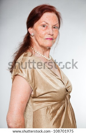 Portrait of good looking senior woman with expressive face showing emotions. Happy and smiling. Acting young. Studio shot isolated on grey background. - stock photo
