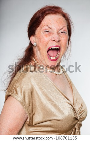 Portrait of good looking senior woman with expressive face showing emotions. Screaming. Acting young. Studio shot isolated on grey background.