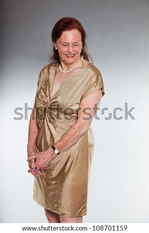 Portrait of good looking senior woman with expressive face showing emotions. Smiling and happy. Acting young. Studio shot isolated on grey background. - stock photo