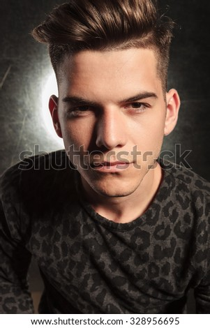 portrait of good looking young man posing in black backgound while wearing leopard print
