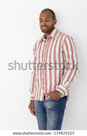 Portrait of goodlooking afro man posing in striped shirt, thinking.