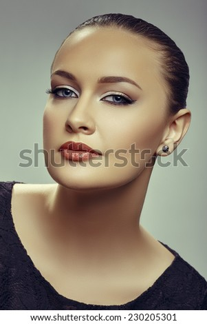 Portrait of gorgeous alluring young woman with blue eyes, clean fresh skin and wearing earrings, looking at camera. - stock photo