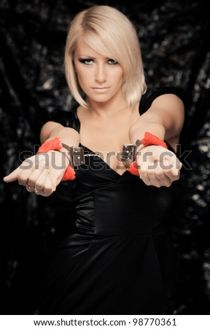 Portrait of gorgeous blond woman in long black dress with handcuffs - stock photo