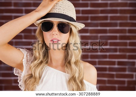 Portrait of gorgeous blonde hipster posing with straw hat against red brick wall - stock photo