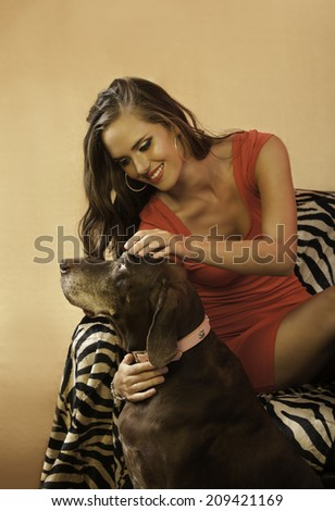 Portrait of gorgeous brunette woman in red dress with long hair, sitting on zebra print chair while playing with a brown dog, smiling happily - stock photo