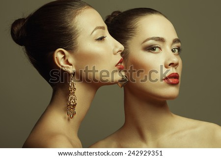 Portrait of gorgeous couple of girlfriends with golden earrings, perfect hairdo and evening make-up posing together over gray background. Close up. Vogue style. Studio shot