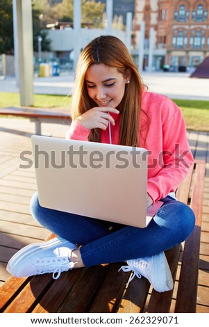 Portrait of gorgeous female student sitting with open laptop computer on campus bench against university building,attractive teenager girl looking for net-book screen with smile feeling good and happy - stock photo