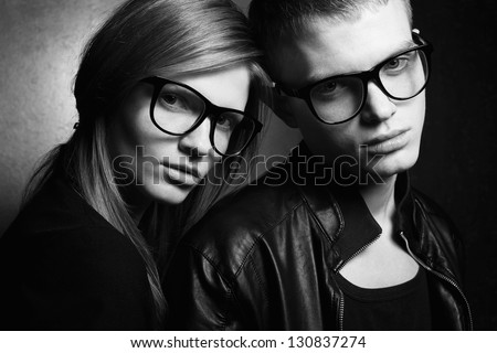 Portrait of gorgeous red-haired fashion twins in black clothes wearing trendy glasses and posing over golden background together. Black and white (monochrome) studio shot.