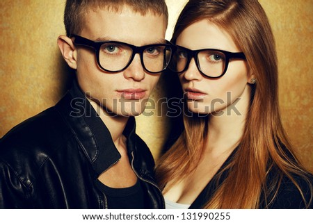Portrait of gorgeous red-haired fashion twins in black clothes wearing trendy glasses and posing over golden background together. Perfect hair. Natural make-up. Perfect skin. Close up. Studio shot. - stock photo