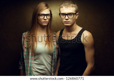 Portrait of gorgeous red-haired fashion twins in casual shirts wearing trendy glasses and posing over golden background together. Studio shot. - stock photo