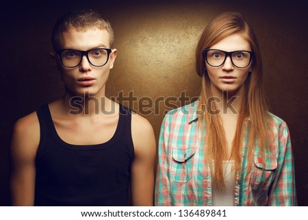 Portrait of gorgeous red-haired (ginger) fashion twins in casual shirts wearing trendy glasses and posing over golden background together with wow (scared) faces. Hipster style. Studio shot. - stock photo