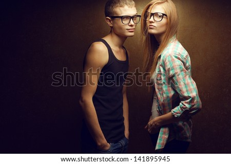 Portrait of gorgeous red-haired (ginger) fashion twins in casual shirts wearing trendy glasses and posing over golden background together. Hipster style. Copy-space. Studio shot - stock photo