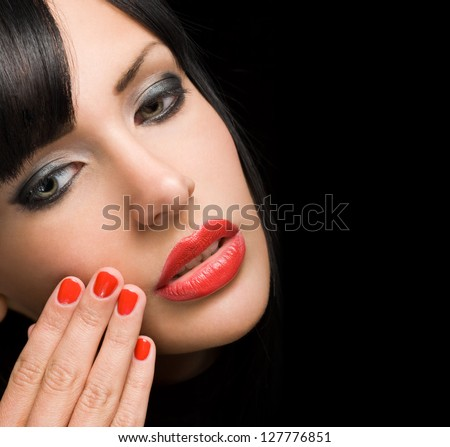 Portrait of gorgeous sensual brunette woman with bright red lips and nails.