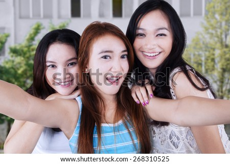 Portrait of gorgeous teenage girls smiling at the camera while taking a self picture together - stock photo
