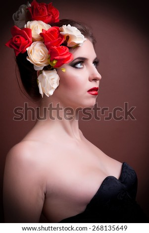 Portrait of gorgeous woman with flowers in head in studio shooting on brown background. Spring theme