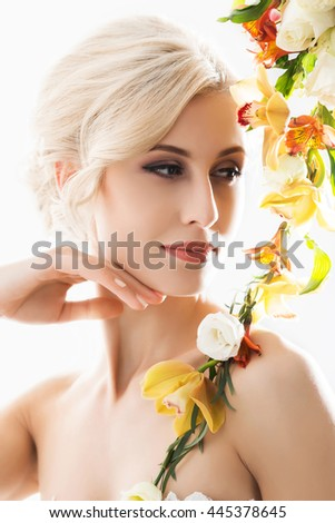 Portrait of gorgeous, young bride in white dress posing with flowers. - stock photo