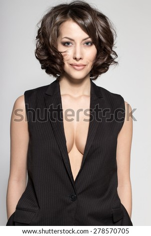 Portrait of gorgeous young caucasian attractive sexy business woman or secretary wearing black jacket without sleeves - stock photo