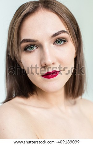 Portrait of gorgeous young caucasian attractive sexy woman with business makeup. Red lips and green eyes