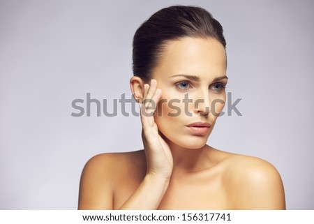 Portrait of gorgeous young lady touching clean and fresh skin of her face and looking away at copyspace against gray background. Beautiful young woman pampering her healthy and perfect skin. - stock photo