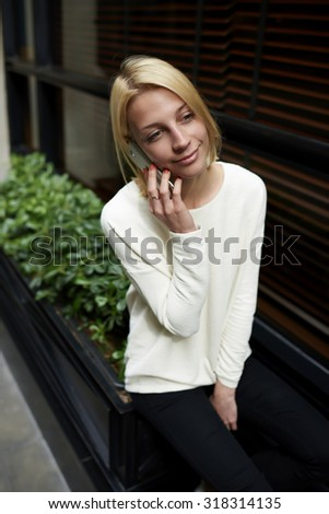 Portrait of gorgeous young woman talking on her mobile phone while sitting in the city, attractive girl at phone call conversation with her smart phone, carefree female person phoning in urban setting - stock photo