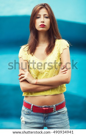 Portrait of gorgeous young woman wearing trendy yellow-green handmade knitted top, jeans, posing over construction symbolizing ocean. Urban style. Close up. Outdoor shot