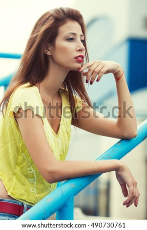 Portrait of gorgeous young woman wearing yellow-green handmade knitted top and posing in the street. Urban style. Close up. Outdoor shot