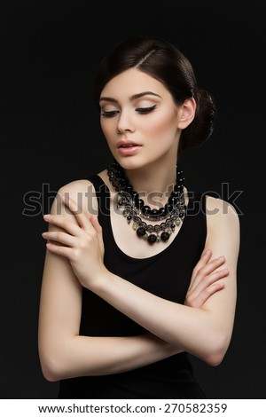 Portrait of gorgeous young woman with necklace over black background - stock photo